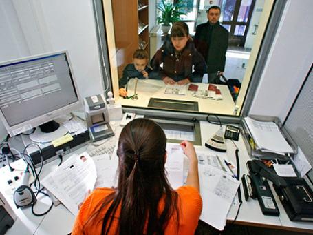 Сотрудница Германского визового центра принимает документы у граждан России. Фото: РИА Новости