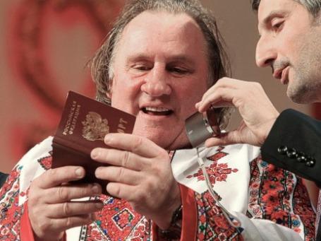 Жерар Депардье рассматривает свой российский паспорт со своим переводчиком на сцене Театра оперы и балета в Саранске. Фото: РИА Новости