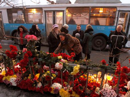 Люди возлагают цветы на место взрыва троллейбуса в Дзержинском районе г. Волгограда. Фото: Reuters
