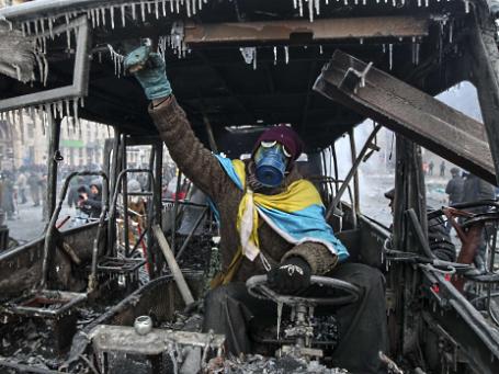 Сторонник евроинтеграции позирует в сожженом милицейском автобусе. Фото: Reuters