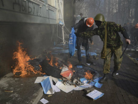 Участники акций протеста сжигают флаги и брошюры Партии регионов в Киеве. Фото: Reuters