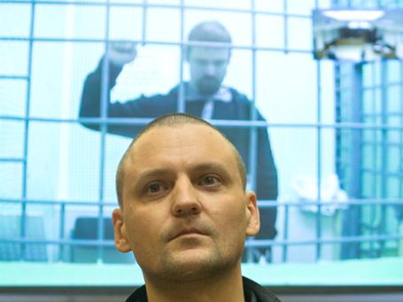 Сергей Удальцов и Леонид Развозжаев (на экране). Фото: РИА Новости