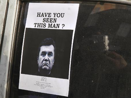Фотография разыскиваемого Виктора Януковича на стекле одной из машин рядом с Майданом. Фото: Reuters