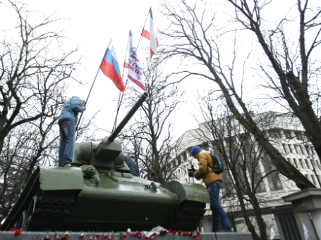 Участники митинга устанавливают российский флаг недалеко от здания Верховного совета Крыма в Симферополе. Фото: Reuters