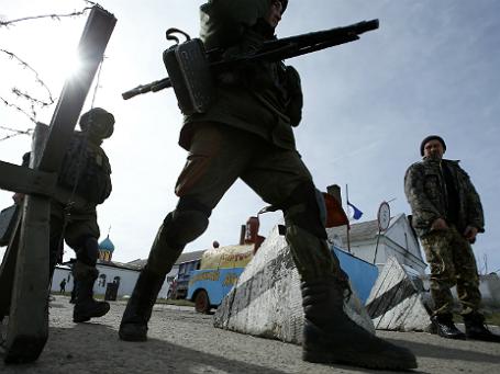 Вооруженные люди за пределами украинского военной базы в селе Перевальное, в Симферопольском районе Крыма 10 марта 2014.Фото: Reuters.