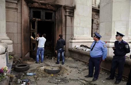 Сотрудники МВД наблюдают, как мужчины снимают переднюю дверь со входа в здание областного совета профсоюзов после массовых беспорядков и пожара в Одессе.