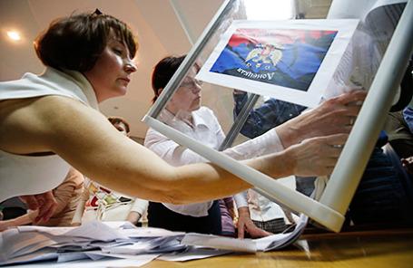 Члены участковой избирательной комиссии опустошают ящик для голосования на референдуме в Донецке.