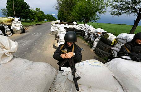 Сотрудник украинского МВД занимает позицию на блокпосте в поселке Былбасовка Донецкой области 14 мая 2014.