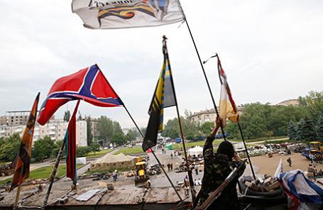 Ополченец ДНР водружает флаги различных подразделений вооруженных сил провозглашенной республики на здание областной администрации Донецка. 29 мая 2014.