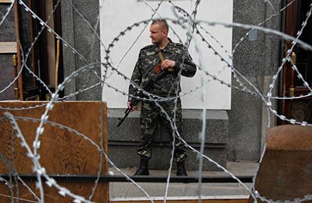 Вооруженный прорусский активист стоит на страже около административного здания в Луганске.