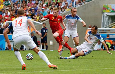 Кевин Де Брюин (сборная Бельгиии) и Сергей Игнашевич (сборная России) во время футбольного матча в Рио-де-Жанейро 22 июня 2014.