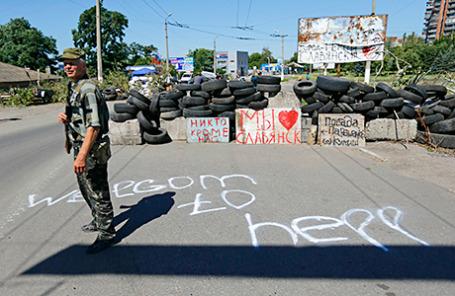 Вооруженный прорусский сепаратист стоит на страже у КПП в Славянске.