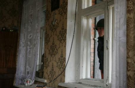 Сотрудник патрульной службы милиции особого назначения «Киев-1» проверяет жилой дом после авиаудара по поселку Семеновка под Славянском.