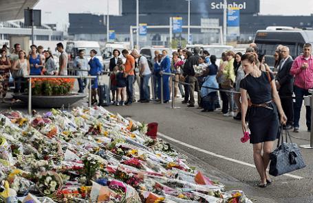 Люди возлагают цветы у здания аэропорта Схипхол (Нидерланды) в память погибших пассажиров  Boeing 777 Малайзийских авиалиний в Донецкой области.