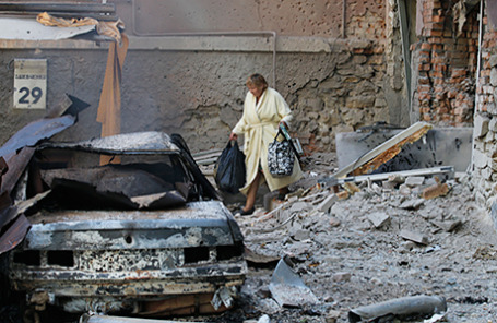 Жительница города у одного из домов, пострадавших в результате артобстрела.