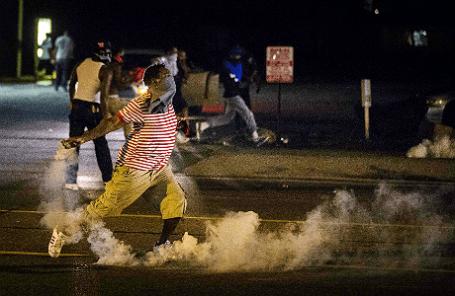 Участник демонстрации в Фергюсоне, штат Миссури, США после применения полицией слезоточивого газа.