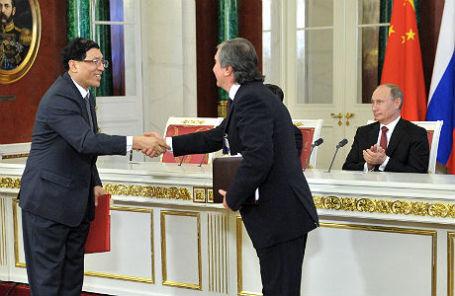 Глава «Роснефти» Игорь Сечин (справа на первом плане) и президент РФ Владимир Путин (справа на втором плане) во время церемонии подписания совместных документов по итогам российско-китайских переговоров в Кремле 22 марта 2013.