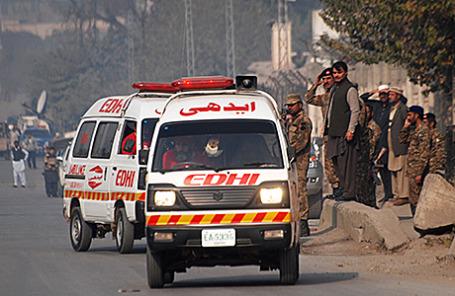 Машины «скорой помощи» у военного училища в городе Пешавар, захваченного боевиками движения «Талибан», 16 декабря 2014.