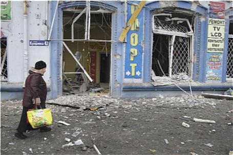 Женщина проходит мимо обстрелянного здания рядом с автобусной остановкой в Донецке