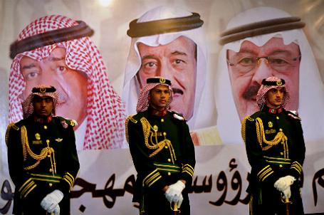 Королевская охрана стоит на посту перед портретами короля Саудовской Аравии Абдаллы, наследного принца Салмана и второго вице-премьера Мукрина бен Абдель-Азиза.