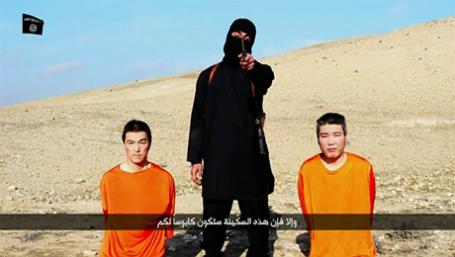 Человек в маске стоит между двумя предполагаемыми японскими заложниками.