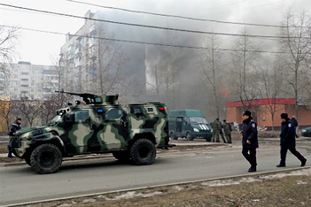 Военный автомобиль у горящего дома на одной из улиц  Мариуполя.