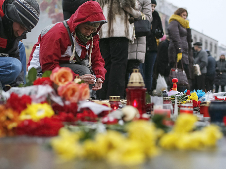 Люди зажигают свечи в память о погибших во время обстрела Мариуполя.