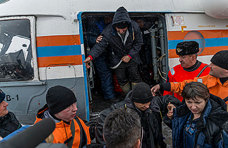 Сотрудники МЧС помогают выжившим после крушения траулера «Дальний Восток» в Охотском море по прибытии в Магадан, 3 апреля 2015.