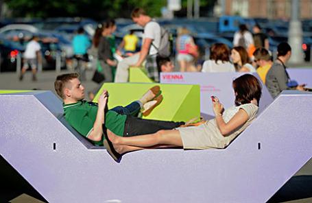 Отдыхающие на арт-скамейке Enzis перед центральным входом в Парк Горького.