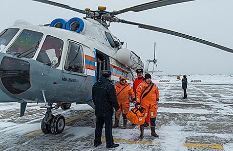 Сотрудники МЧС около вертолета, на котором проводилась спасательная операция на месте крушения траулера «Дальний Восток».