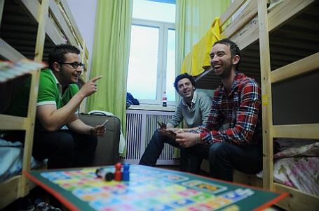 Иностранные туристы в одной из спальных комнат хостела.