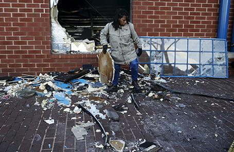 Жительница Балтимора около разграбленного в ходе беспорядков магазина. 28 апреля 2015.