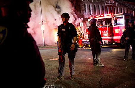 Полиция и пожарные около горящего магазина в Балтиморе, Мэриленд, США, 28 апреля 2015.