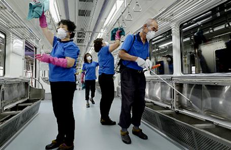Сотрудники метро в Сеуле занимаются дезинфекцией вагона поезда.