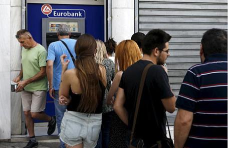 Люди стоят в очереди к банкомату Eurobank в Афинах.