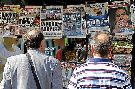 Жители Афин смотрят на газеты, написавшие о результатах вчерашнего референдума.