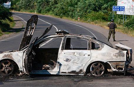 Cотрудник правоохранительных органов около сожженной машины в поселке Мукачево Закарпатской области.