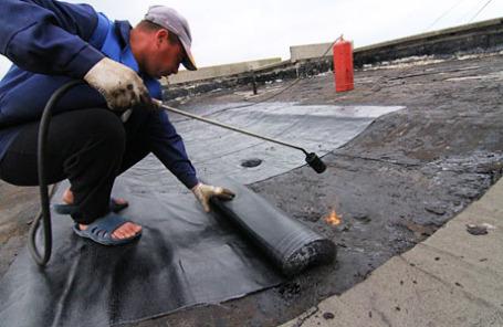 Укладка нового рубероида на крыше во время капитального ремонта многоэтажного панельного дома в Ясенево.