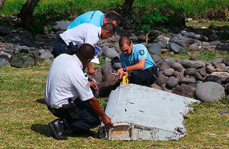 Французские жандармы несут большой обломок, найденный на пляже в Сент-Андре на острове в Индийском океане после авиакатастрофы рейса MH370.