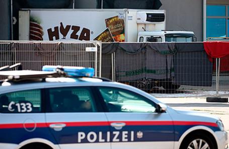 Полицейская машина охраняет грузовик, в котором обнаружили более 70 тел нелегальных мигрантов у здания таможни в селе Никельсдорф, Австрия.