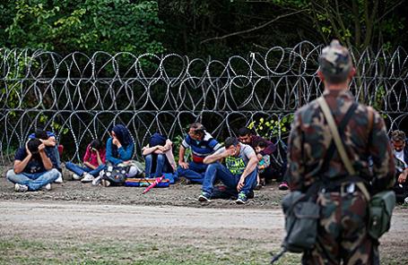 Венгерский военнослужащий охраняет мигрантов, задержанных во время незаконного пересечения сербско-венгерской границы, 15 сентября 2015.