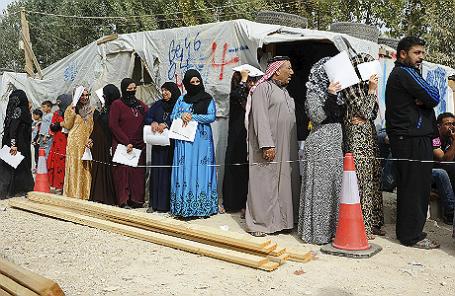 Сирийские беженцы в поселении в Долине Бекаа в очереди за досками и инструментами, пожертвованными Агентством ООН по делам беженцев для укрепления палаток.