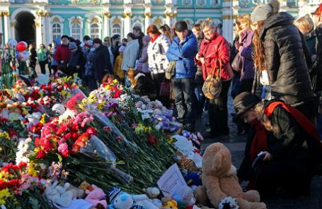 У стихийного мемориала в память о жертвах авиакатастрофы самолета Airbus A321 на Дворцовой площади.