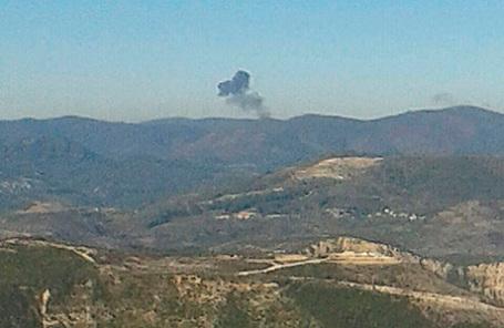 Дым поднимается на месте сбитого бомбардировщика Су-24.