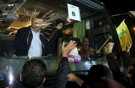 Бойцы и сторонники группировки «Хезболла» в международном аэропорту Бейрута приветствуют женщину в автобусе с военными и гражданскими, вывезенными из окруженных шиитских городов.