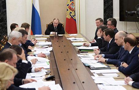 Президент РФ Владимир Путин (в центре) во время совещания с членами правительства РФ.