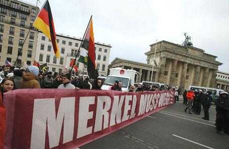 Сторонники правого крыла на митинге против миграционной политики правительства Германии в Берлине (надпись «Меркель должна уйти»).