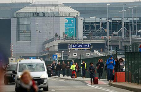 Люди покидают аэропорт Завентем после взрыва недалеко от Брюсселя.