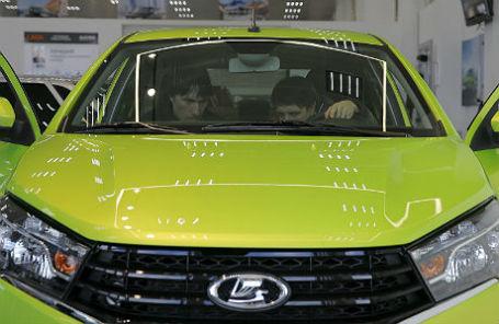 Посетители автосалона осматривают Lada Vesta.