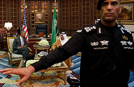 Охранник отгоняет фотографов во время встречи президента США Барака Обамы и короля Саудовской Аравии Салмана в Эр-Рияде, 20 апреля 2016.